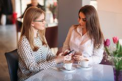 Girls use their break from work to drink coffee and chat. Caffe cappuccino. Girls use their break from work to drink coffee and chat. Caffe cappuccino royalty free stock images