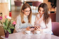 Girls use their break from work to drink coffee and chat. Caffe cappuccino. Girls use their break from work to drink coffee and chat. Caffe cappuccino stock photos
