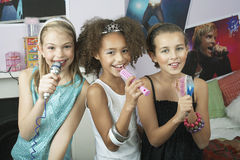 Girls Using Brushes As Microphones At Slumber Party. Multiethnic young girls using brushes as microphones to sing at a slumber party Stock Photo