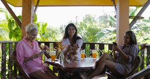 Girls Using Cell Smart Phones Watching Photos Talking On Terrace In Tropical Forest, Women Group Chatting Online In. Morning Slow Motion 60 stock video footage