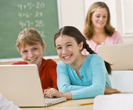Girls using laptop in classroom. Two girls smiling as they share a laptop in the classroom Royalty Free Stock Photos