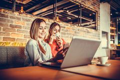 Girls using laptop and drinking coffee. Two smiling girls using laptop and drinking coffee while sitting in a modern cafe interior. Friendship and technology Stock Images