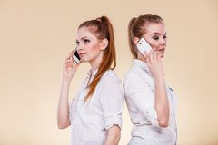 Girls using mobile phone talking. Technology and communication. Lovely teen girls using mobile phones talking, Human emotion, reaction and relationship Royalty Free Stock Photos
