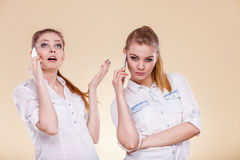 Girls using mobile phone talking. Technology and communication. Lovely teen girls using mobile phones talking, Human emotion, reaction and relationship Stock Photography