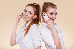 Girls using mobile phone talking. Technology and communication. Lovely teen girls using mobile phones talking, Human emotion, reaction and relationship Stock Image