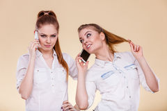 Girls using mobile phone talking. Technology and communication. Lovely teen girls using mobile phones talking, Human emotion, reaction and relationship Royalty Free Stock Image