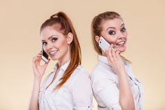 Girls using mobile phone talking. Technology and communication. Lovely teen girls using mobile phones talking, Human emotion, reaction and relationship Stock Photo