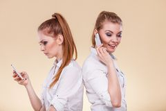 Girls using mobile phones talking reading message. Technology and communication. Lovely teen girls sharing social media, using mobile phones talking and looking Royalty Free Stock Photos