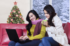 Girls using notebook with christmas tree background Royalty Free Stock Image