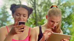 Girls using smartphone and ipad in park. Friends surfing internet on tablet. Girls using phone and ipad in park. Closeup of friends surfing internet on tablet stock footage