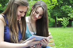 Girls using a tablet. Two young girls using a tablet computer outdoor in park Royalty Free Stock Photo