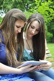 Girls using a tablet pc. Two young girls using a tablet computer outdoor in summer park Stock Photos