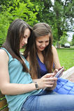 Girls using a tablet pc. Two young girls on bench using a tablet computer outdoor in park Royalty Free Stock Image