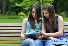 Girls  using a tablet pc. Two young girls on bench using a tablet computer outdoor in park Royalty Free Stock Images