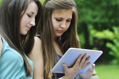 Girls using a tablet pc. Two young girls on bench using a tablet computer outdoor in park Stock Photos