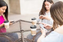 Girls using their smartphones at cafe. Young girl hanging out with her friends at outdoors cafe using their phones, with cups of coffee on table Royalty Free Stock Photos