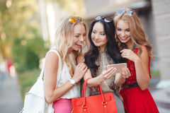Girls view photos on a mobile phone Royalty Free Stock Photos