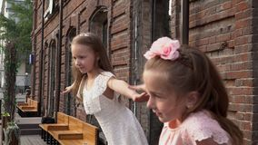 Girls wait for friends at the big brick building. Lovely little girls pose for the camera. On this video you can see as two little girls in light dresses try to stock footage