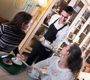 Girls and waiter in coffee-house Royalty Free Stock Photos