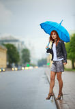Girls Waiting a Bus. Redhead girls with umbrella waiting a bus stock image
