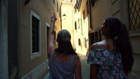 Girls walk along narrow street among architectural buildings