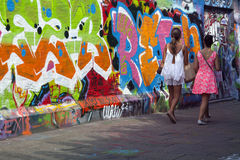 Girls walk along walls full of grafiti in Ghent Royalty Free Stock Photo
