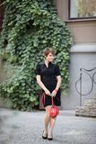 Girls walk on cozy street. Girl with red handbag walking on the street vine-covered Stock Photos