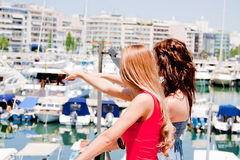 The girls walked down the street along the marina Stock Image
