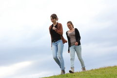 Girls walking. Two sporty young women walking down a grassy hill - set against a cloudy sky Stock Photography