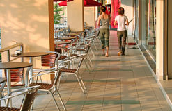 Girls walking. A pair of young girls walking down a sidewalk cafe royalty free stock images