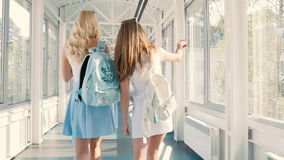 Girls are walking across the long corridor. The girls are talking and smiling. The girls greets with couple of man and girl. The girls goes by two guys and stock video