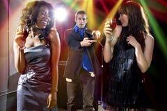 Girls Walking Away from Broke Man at a Nightclub Royalty Free Stock Photography