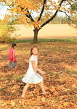 Girls walking barefoot in dead leaves Stock Images
