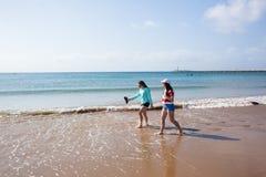 Girls Walking Beach Shoreline Ocean. Teenage girls rear unidentified walking beach water line ocean shoreline landscape Stock Photo