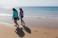 Girls Walking Beach Shoreline Ocean. Teenage girls rear unidentified walking beach water line ocean shoreline landscape Royalty Free Stock Photos