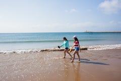 Girls Walking Beach Shoreline Ocean. Teenage girls rear unidentified walking beach water line ocean shoreline landscape Stock Images