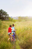 Girls walking bicycles in field Stock Photo