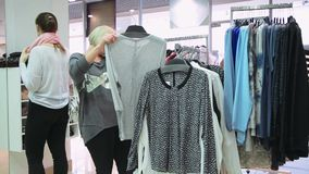 Girls walking in a clothing store. Trying on clothes in front of the mirror and talking on the phone while shopping stock video footage