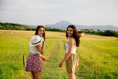 Girls walking in a green meadow. Happy young girls walking in a green meadow Stock Images