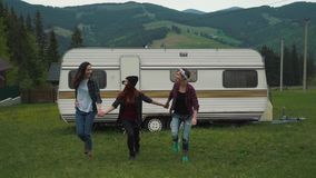 Girls are walking holding hands near a trailer in the mountains.  stock footage