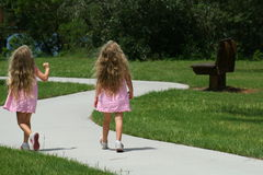 Girls walking in the park. Two little girls walking in the park looking up Royalty Free Stock Photos