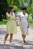 Girls walking in the park joining hands Stock Photography