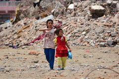 Girls walking pass collapsed building after earthquake disaster Stock Images