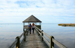 Girls walking on pier on the lake. Sisters walking on pier on the lake. One of girls has backpack Royalty Free Stock Photo