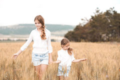 Girls walking in rye field. Two sisters in similar clothes walking in rye field outdoors. Togetherness. Friendship Stock Photography