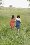 Girls Walking Together In Grassy Field Stock Images