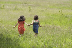 Girls Walking Together In Grassy Field Royalty Free Stock Images