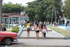 Girls walking in a town square past a classic car in Havana, Cuba Royalty Free Stock Photos