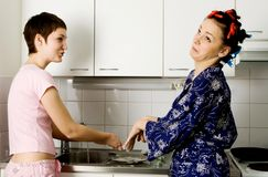Girls Washing The Plate. Young girls wash ware. Home interrior shot stock image