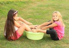 Kids - girls washing their feet royalty free stock photography